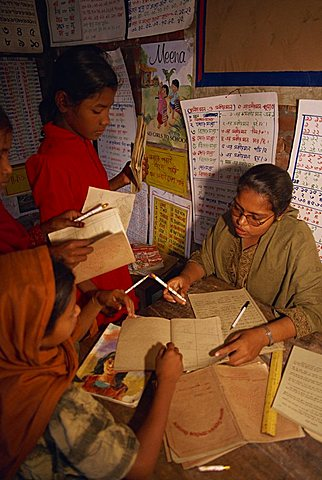 A Bangladeshi woman teacher marks students books in a school in the slums of Dhaka (Dacca), Bangladesh, Asia