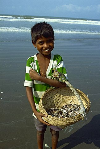 Boy with basket on the beach, Cox's Bazaar, Bangladesh, Asia
