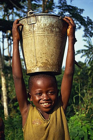 Head and shoulders portrait of a young African child carrying a bucket of water on his head, smiling and looking at the camera, Liberia, West Africa, Africa