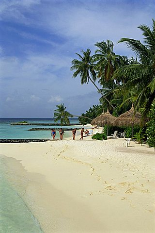 Women on the beach with thatched umbrellas and palm trees at Nakatchafushi on the Maldive Islands, Indian Ocean, Asia