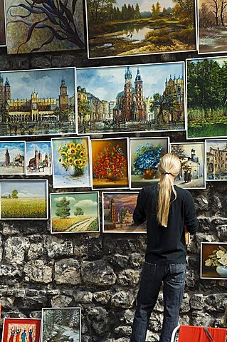 Paintings displayed on the old city walls near Florians's Gate, Krakow (Cracow), Poland, Europe