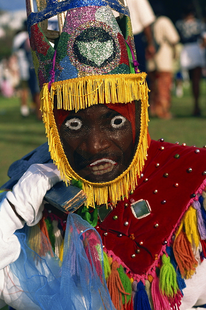 Head and shoulders portrait of a person wearing mask headdress and brightly coloured costume, Gombey, island of Bermuda, Atlantic, Central America