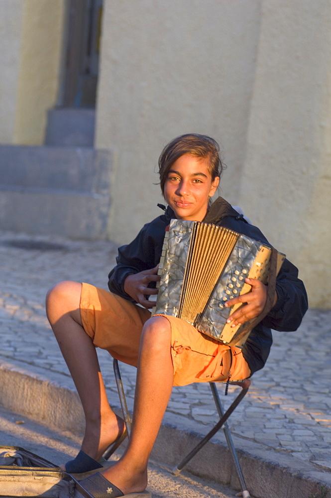 Gypsy girl playing piano accordion, Alvor, Algarve, Portugal, Europe