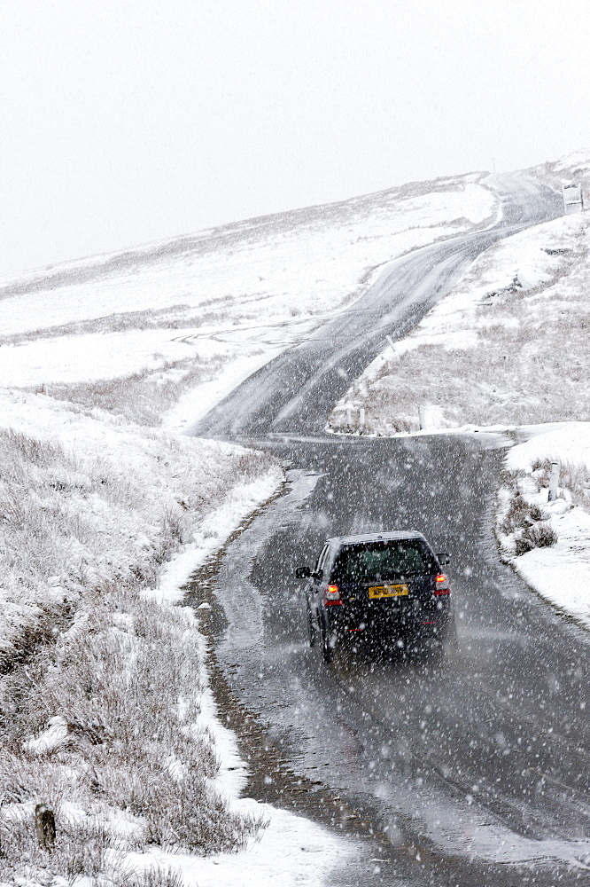 A car negotiates a road through a wintry landscape in the Elan Valley area in Powys, Wales, United Kingdom, Europe