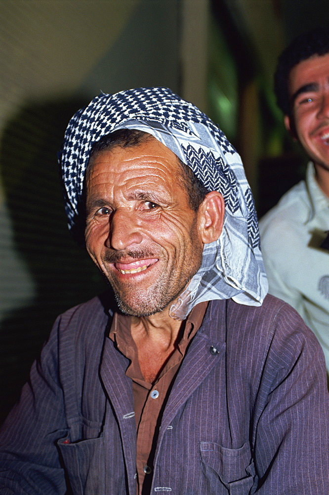 Head and shoulders portrait of a Kurdish man wearing a kaffiyeh, smiling and looking at the camera, in the Souk, Erbil, Kurdistan, Iraq, Middle East