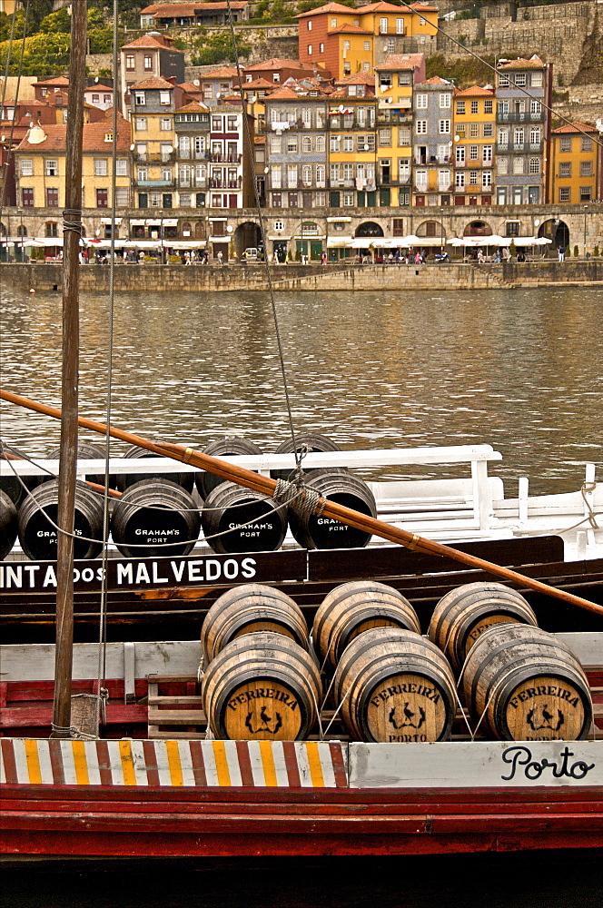 Port wine barrels on a boat on River Douro with Vila Nova de Gaia in the background, Porto, Portugal, Europe