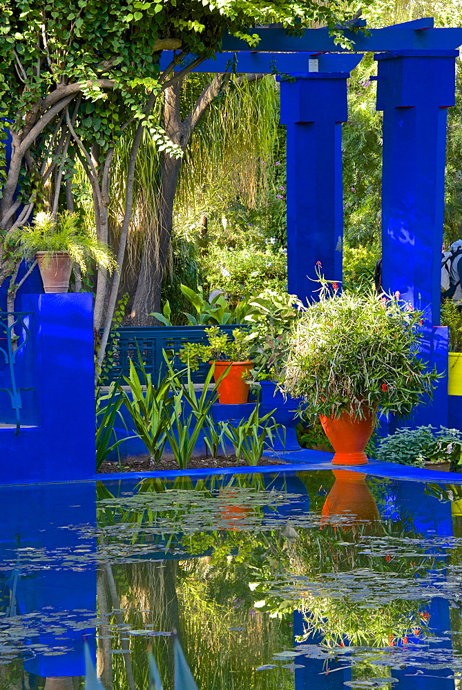 Coloured pots and plants reflected in water basin, in Majorelle Garden, Marrakech, Morocco, North Africa, Africa