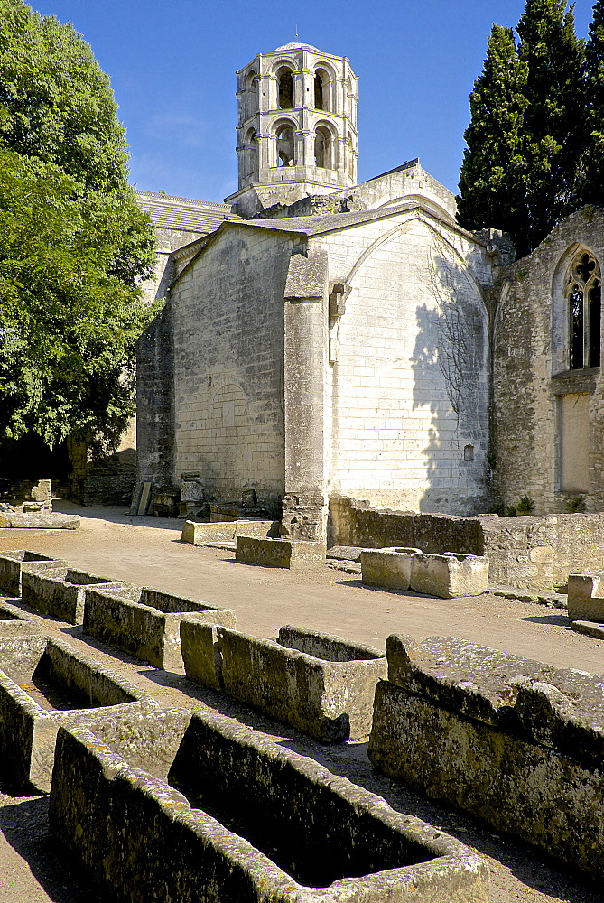 Gallo-roman sarcophagi, Alyscamps, gallo-roman necropolis, and the lantern steeple of the 12th century Saint Honorat church,  Arles, Bouches du Rhone, Provence, France, Europe - 665-5441