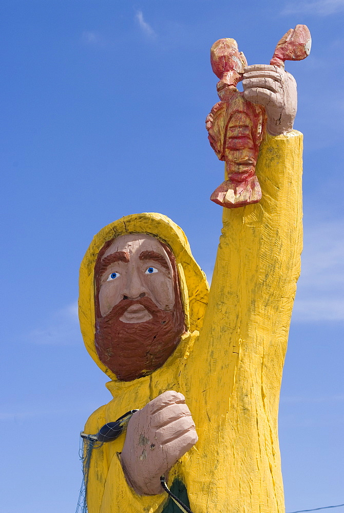 Wood folk-style carving in front of The Rusty Anchor restaurant, Pleasant Bay, Cape Breton, Nova Scotia, Canada, North America