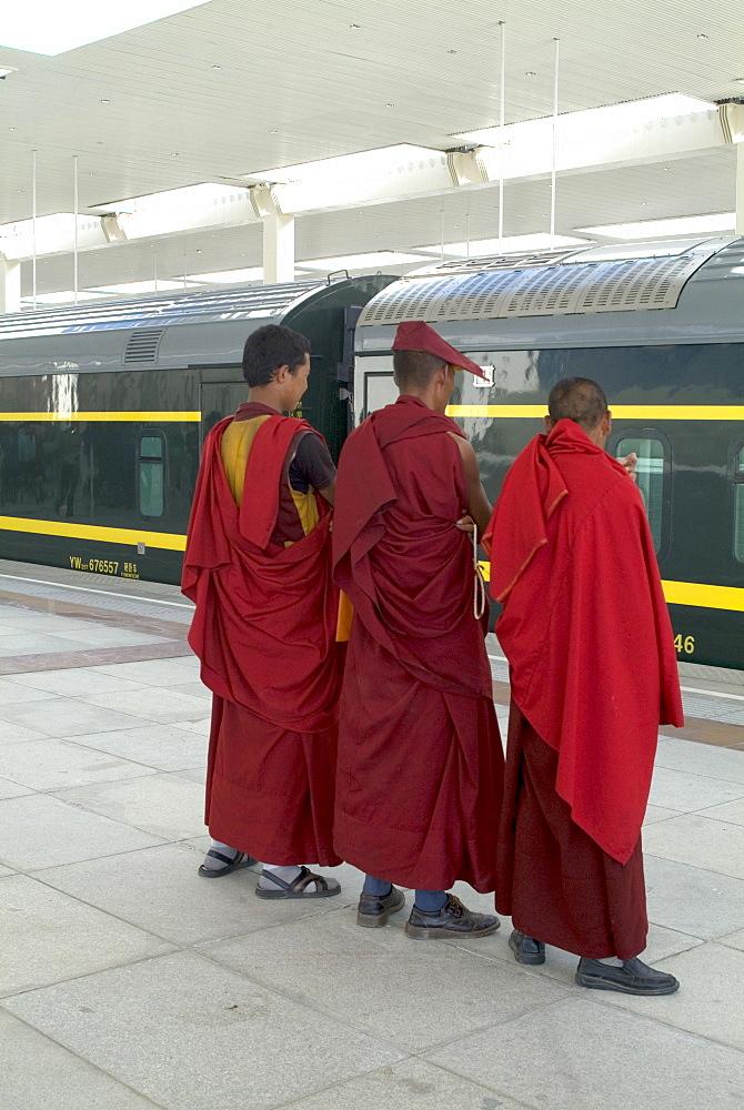 Lamas awaiting arrival of train, New Railway station, Beijing to Lhasa, Lhasa, Tibet, China, Asia