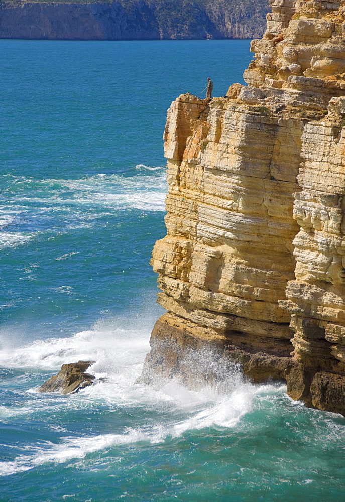 Fisherman on the edge of the cliff fishing on the Cape St. Vincent peninsula, Sagres, Algarve, Portugal, Europe