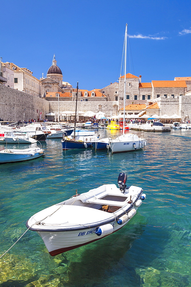Fishing boat and clear water in the Old Port, Dubrovnik Old Town, Dalmatian Coast, Dubrovnik, Croatia, EU, Europe