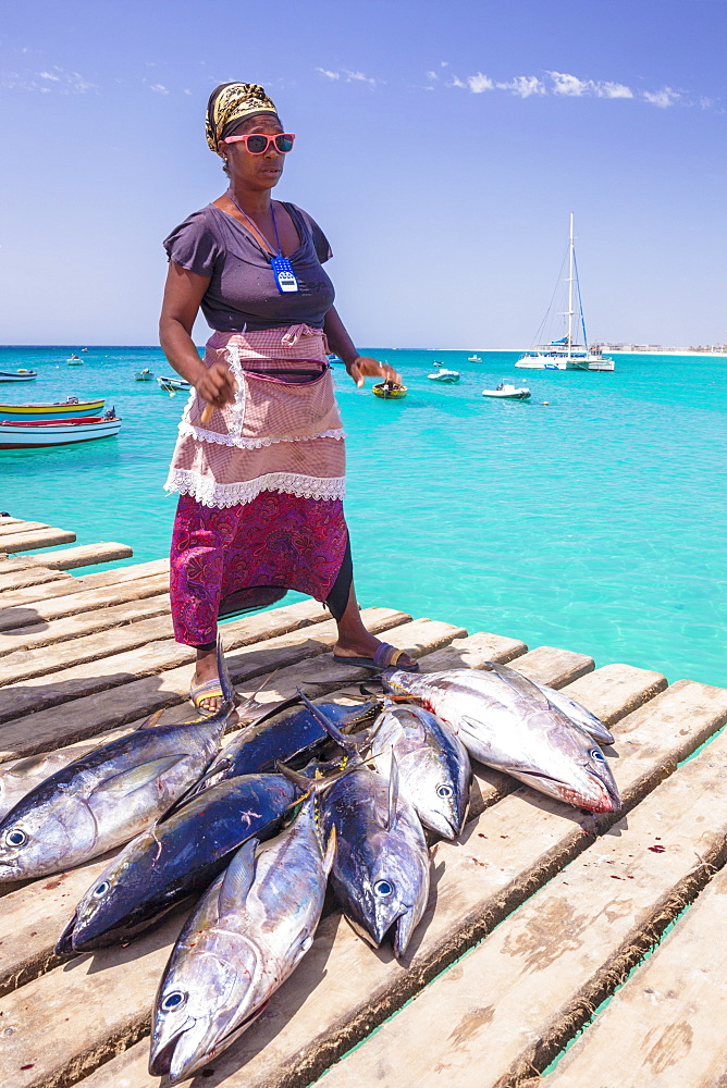 Colourful local woman selling freshly caught yellow fin tuna fish from the pier at Santa Maria, Sal island, Cape Verde, Africa