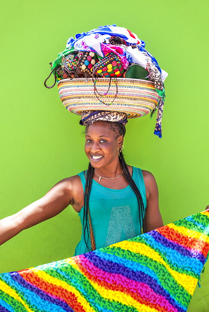 Local woman with basket on her head selling souvenir scarves and jewellery, Espargos, Santa Maria, Sal island, Cape Verde, Africa