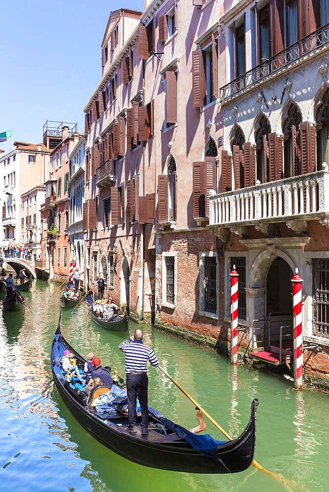 Gondolier, rowing a gondola, with tourists, along canal, in front of a palazzo, Venice, UNESCO World Heritage Site, Veneto, Italy, Europe