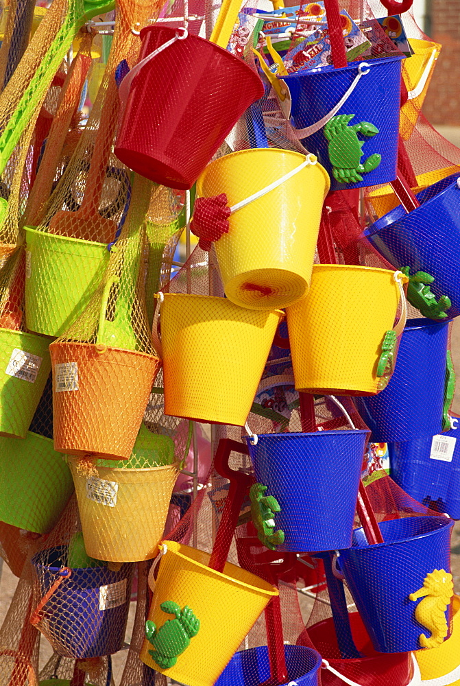 Fifteen brightly coloured buckets, mainly yellow and blue, for sale, Skegness, Lincolnshire, England, United Kingdom, Europe