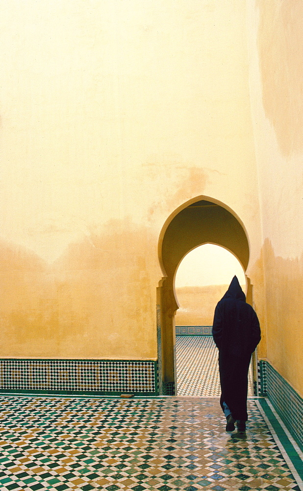 Hooded figure visiting the Tomb of Moulay Ismail, Meknes