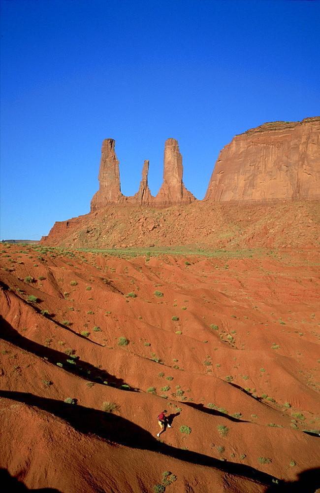 Rock climber in huge landscape, Three Sisters, Monument Valley, Navajo Reserve, Arizona/Utah, USA