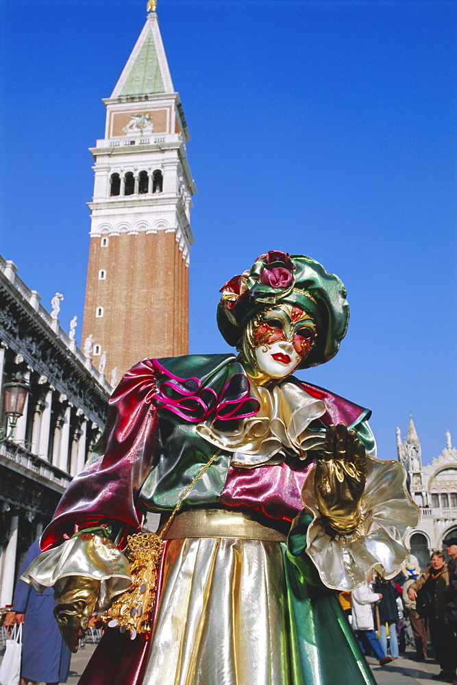 Person wearing masked carnival costume, St. Mark's Square and Campanile behind, Venice Carnival, Venice, Veneto, Italy