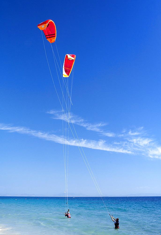 Two kiteboarders trying to take off, Tarifa, Costa de la Luz, Cadiz Province, Andalucia (Andalusia), Spain. Europe