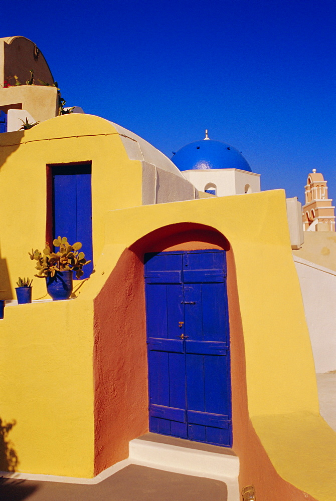 Blue and yellow traditional house with churches in the background, Oia village, Oia, Santorini (Thira), Cyclades Islands, Greece - 718-685