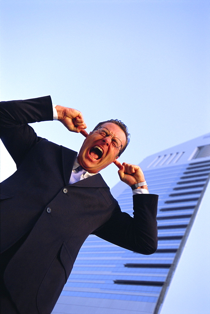 Business man with fingers in his ears, outdoors, shouting