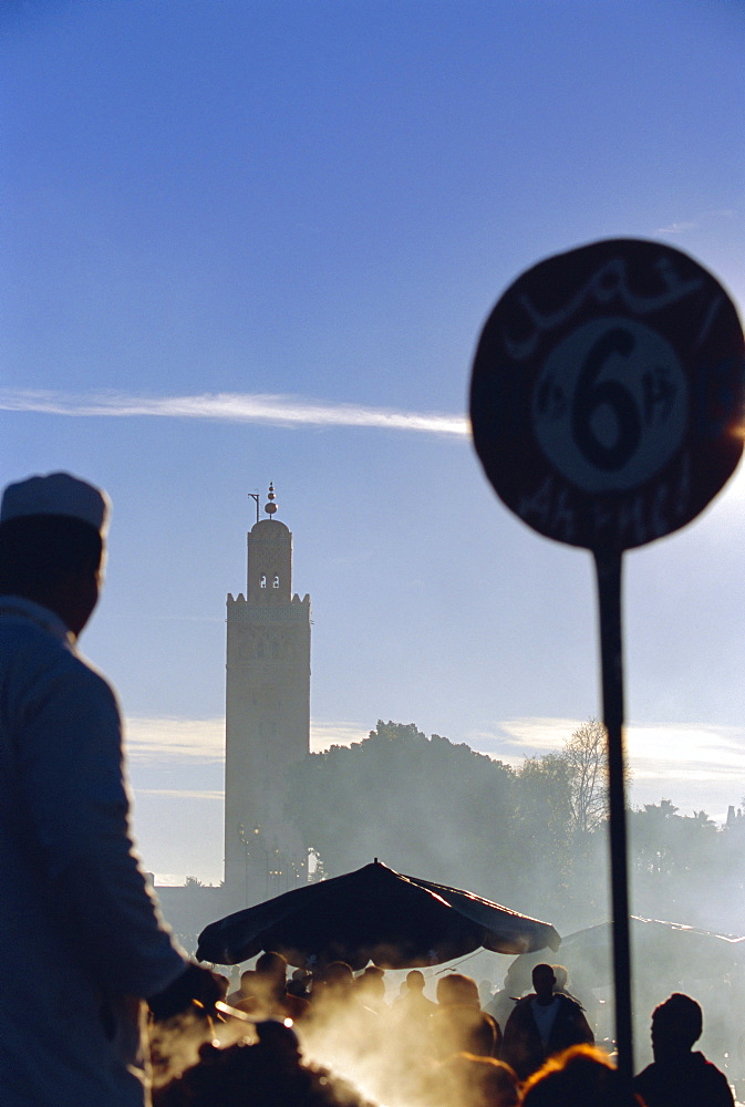 A chef cooking at a food stall in the Djemma-el-Fna square, with the Koutoubia minaret behind, Marrakech, Morocco