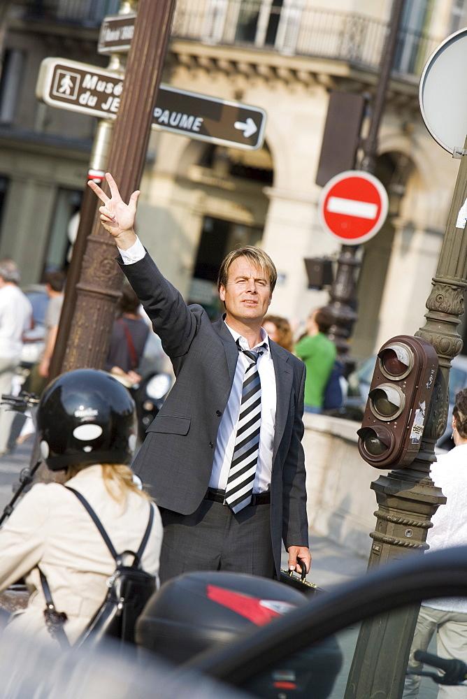 Business man waving, Paris, France, Europe