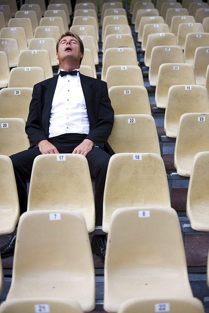 Man asleep surrounded by empty chairs
