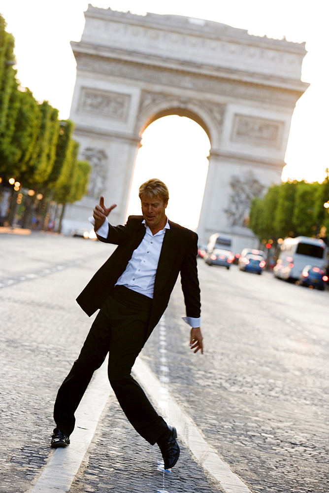 Man dancing on Champs Elysees with Arc de Triomphe behind, Paris, France, Europe