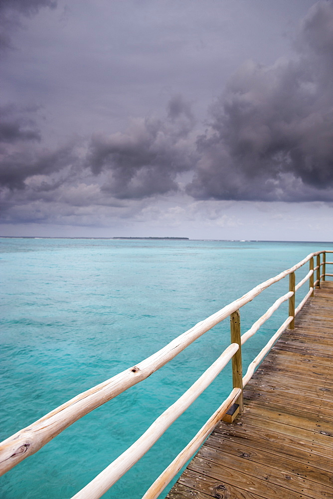 Stormy sky over wooden pier, The Maldives, Indian Ocean, Asia
