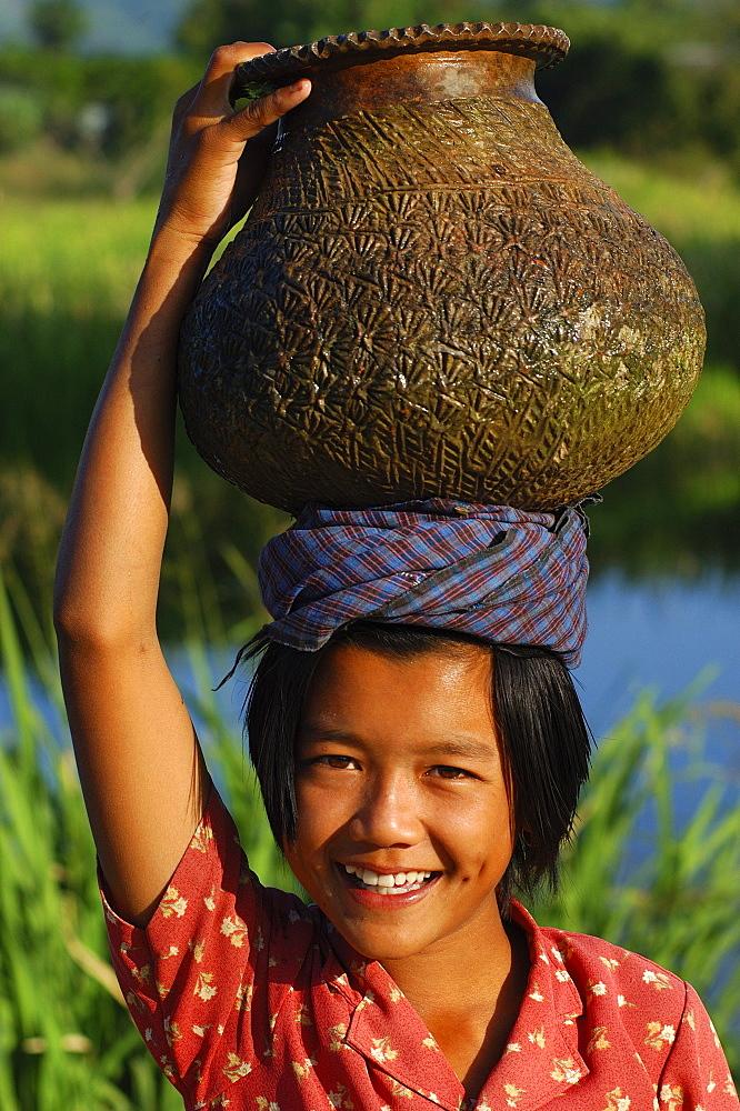 Young girl with water jar on head, Inle Lake, Shan State, Myanmar (Burma), Asia