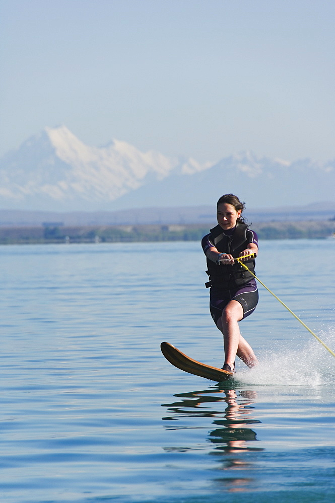 Water skier on Lake Benmore and a distant Aoraki (Mount Cook), 3754m, Australasia's highest mountain, Mackenzie Country, Otago, South Island, New Zealand, Pacific