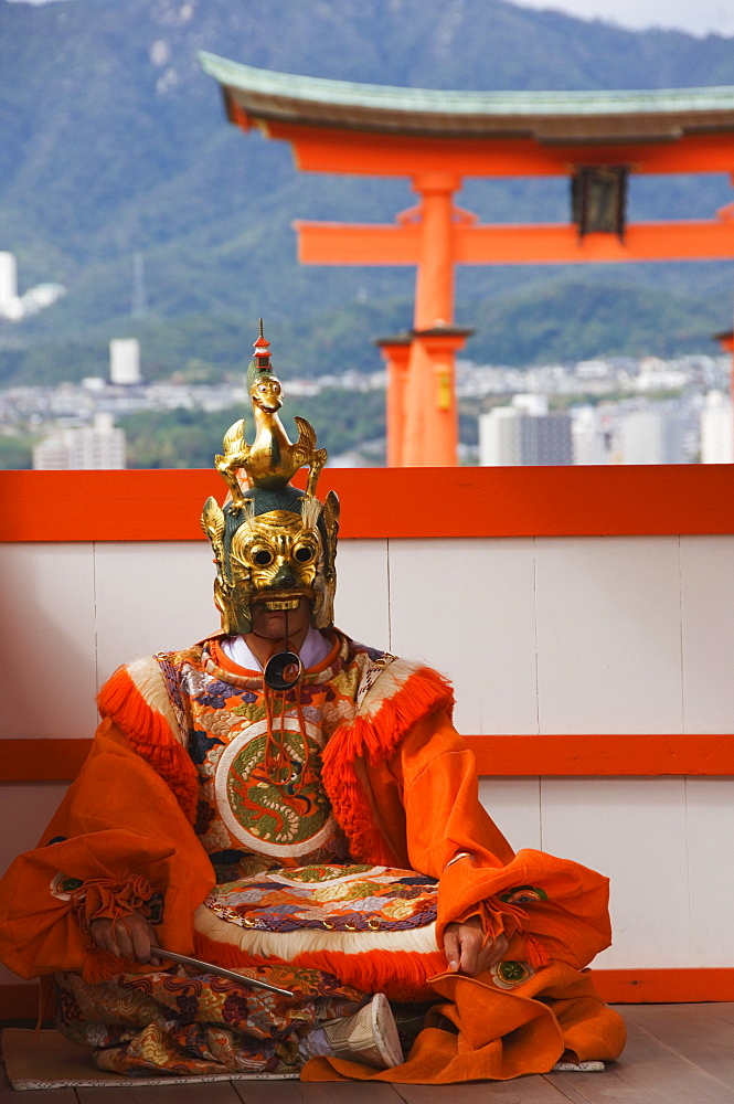 A Wedding Ceremony Dance Performer in front of the Floating Torii Gate at Itsukushima Shrine, founded in 593, UNESCO World Heritage Site, Miyajima Island, Hiroshima prefecture, Honshu Island, Japan, Asia