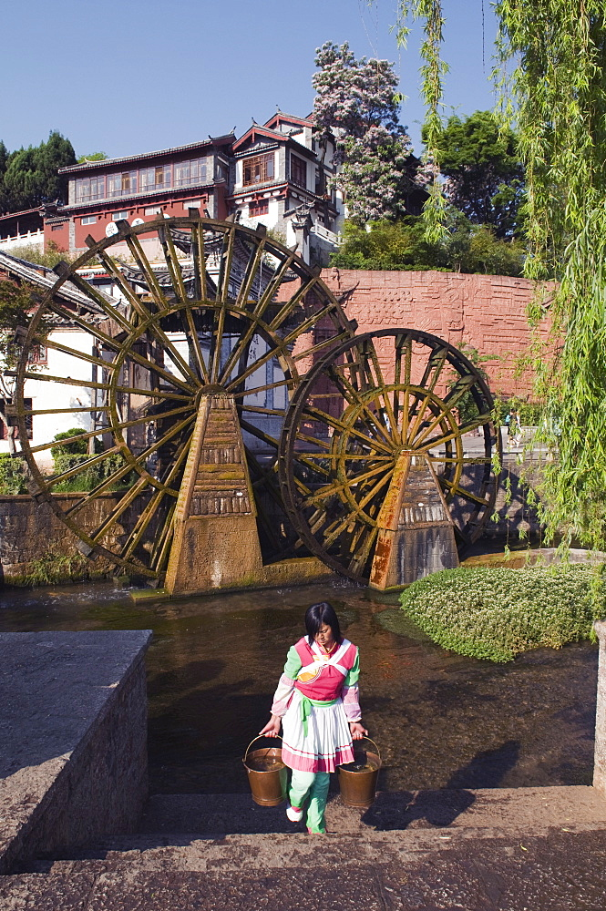 A Bai girl carrying buckets of water in front of a water wheel in Lijiang Old Town, UNESCO World Heritage Site, Yunnan Province, China, Asia