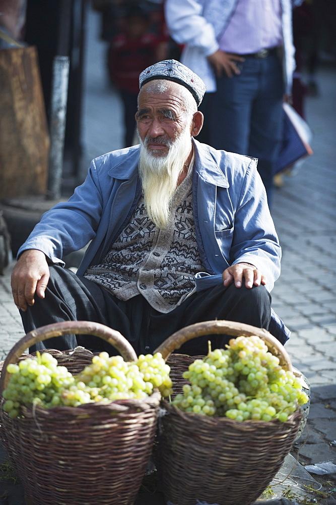 Bearded man selling grapes at the Sunday market, Kashgar (Kashi), Xinjiang Province, China, Asia