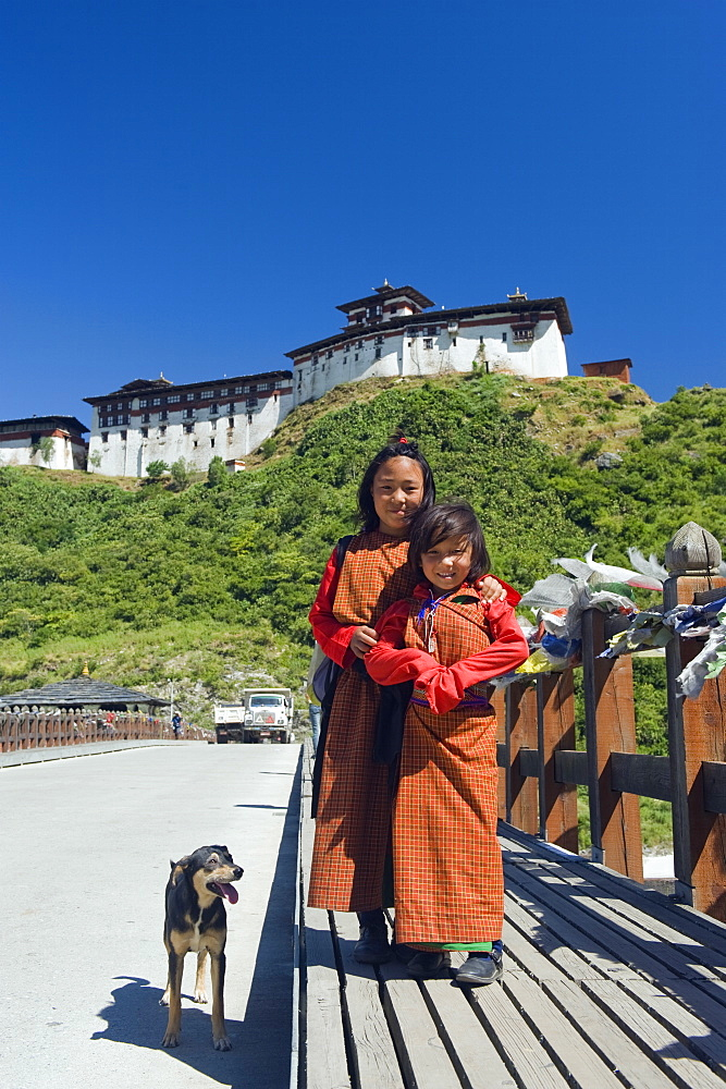 Two girls and dog on a bridge below Wangdue Phodrang Dzong, founded by the Zhabdrung in 1638, Bhutan, Asia