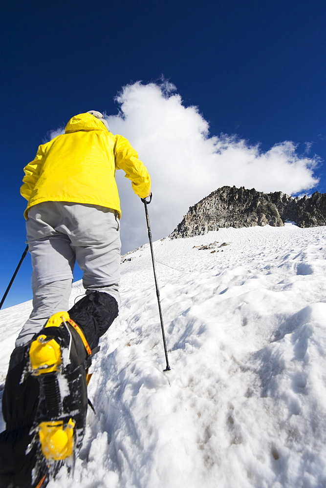 A climber walking up a snowfield, Pico de Aneto, the highest peak in the Pyrenees, Spain, Europe