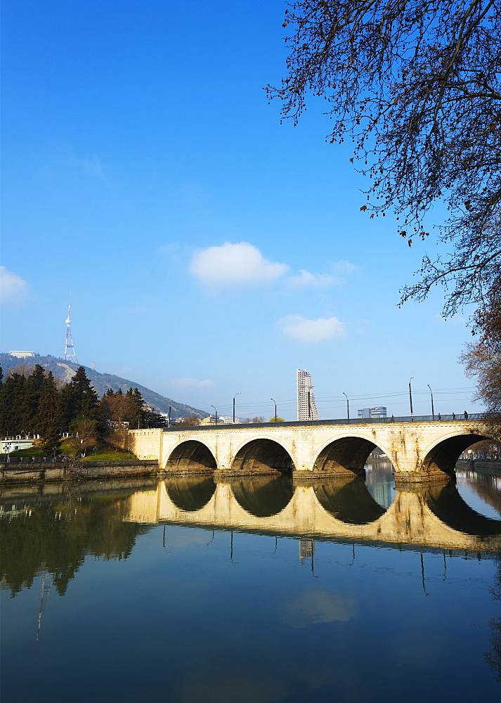 Arched bridge reflecting in Mtkvari River, Tbilisi, Georgia, Caucasus, Central Asia, Asia