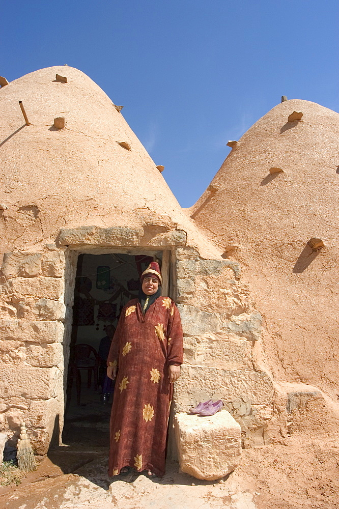 Local woman in front of her beehive house built of brick and mud, Srouj village, Syria, Middle East