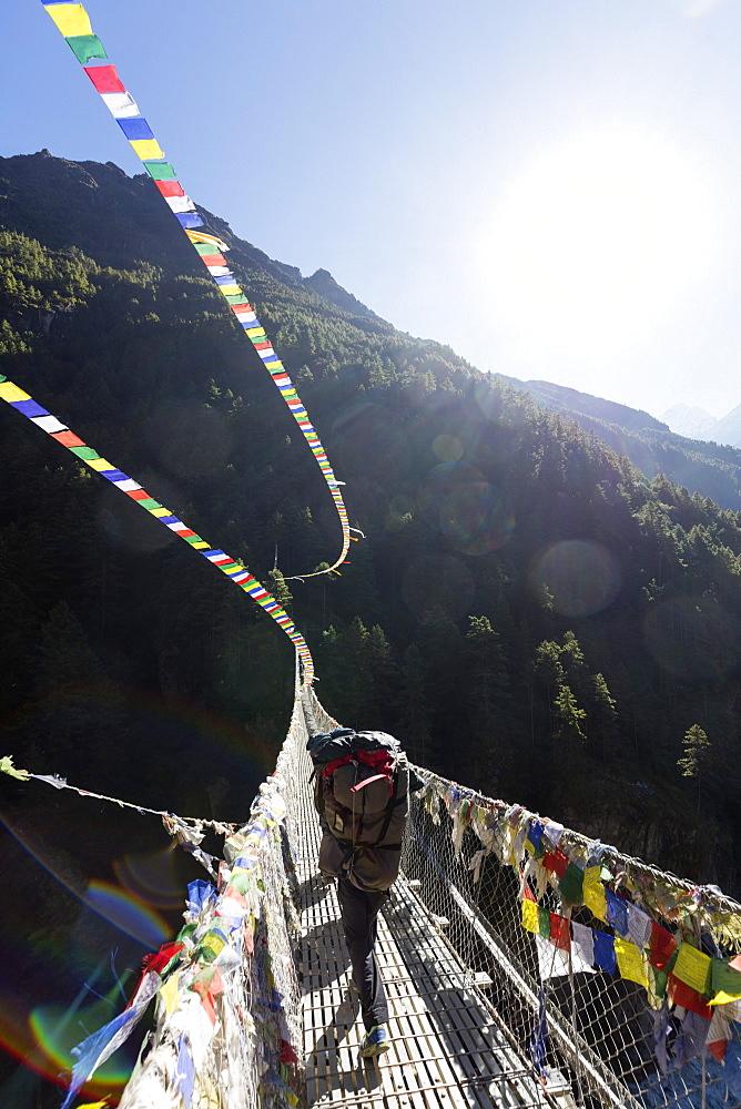 Asia Nepal Khumbu valley Sagamartha National Park Unesco, porter crossing a suspension bridge decorated in Tibetan prayer flags