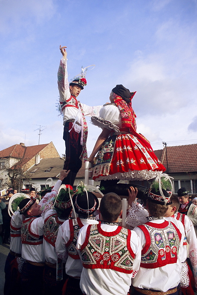 Maiden and lad standing on chairs held by other lads to cheer their union, in traditional dress, St. Martin Feast with Wreath Festival, Svatoborice-Mistrin, Brnensko, Czech Republic, Europe