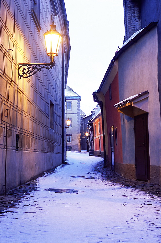 Snow covered 16th century cottages on Golden Lane (Zlata ulicka) in winter twilight, Hradcany, Prague, Czech Republic, Europe
