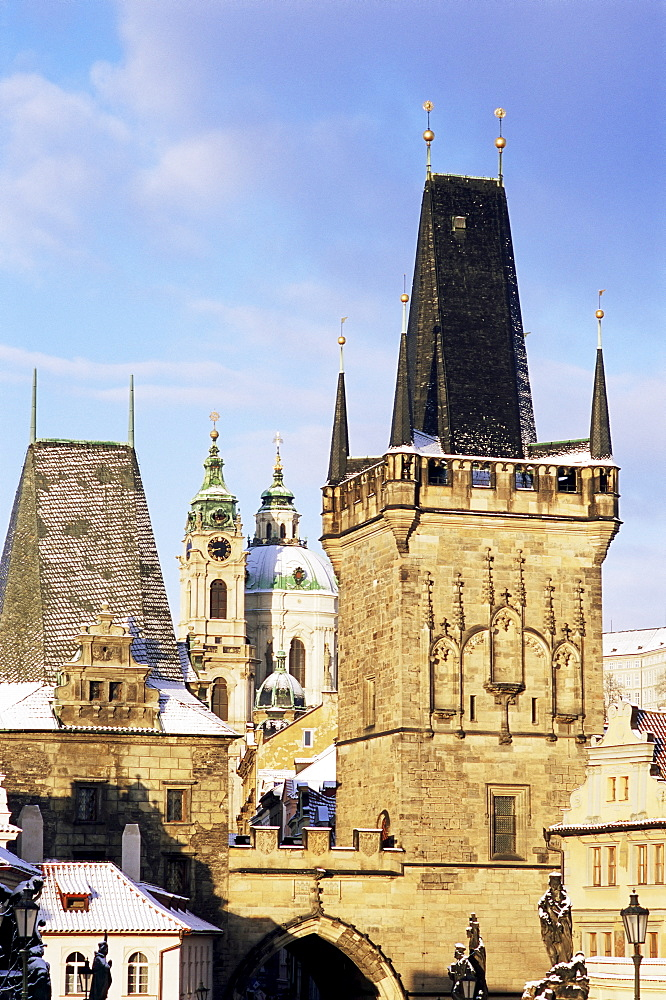 Snow-covered Romanesque and Gothic Malostranske Bridge towers and in the background the towers of the Baroque St. Nicholas church, Mala Strana, Prague, Czech Republic, Europe