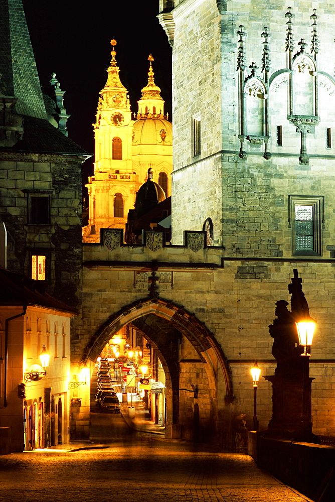 Romanesque and Gothic Malostranske bridge towers, with the two towers of Baroque St. Nicholas church beyond, at night, Mala Strana, Prague, Czech Republic, Europe