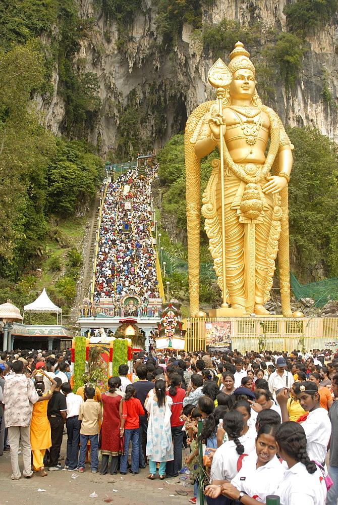 Statue of Hindu deity with pilgrims walking 272 steps up to Batu Caves during Hindu Thaipusam Festival, Sri Subramaniyar Swami Temple, Batu Caves, Selangor, Malaysia, Southeast Asia, Asia