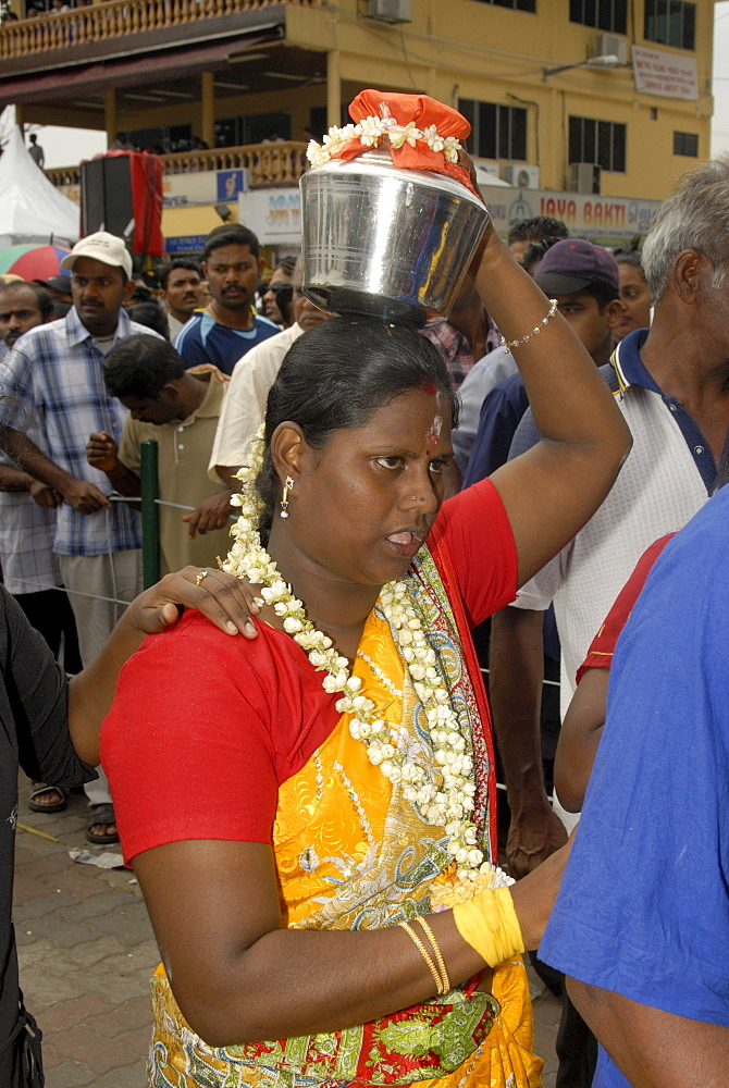 Pilgrim known as kavadi carrier is carrying container (paal kudam) of milk offerings during Hindu Thaipusam Festival from Sri Subramaniyar Swami Temple to Batu Caves, Selangor, Malaysia, Southeast Asia, Asia