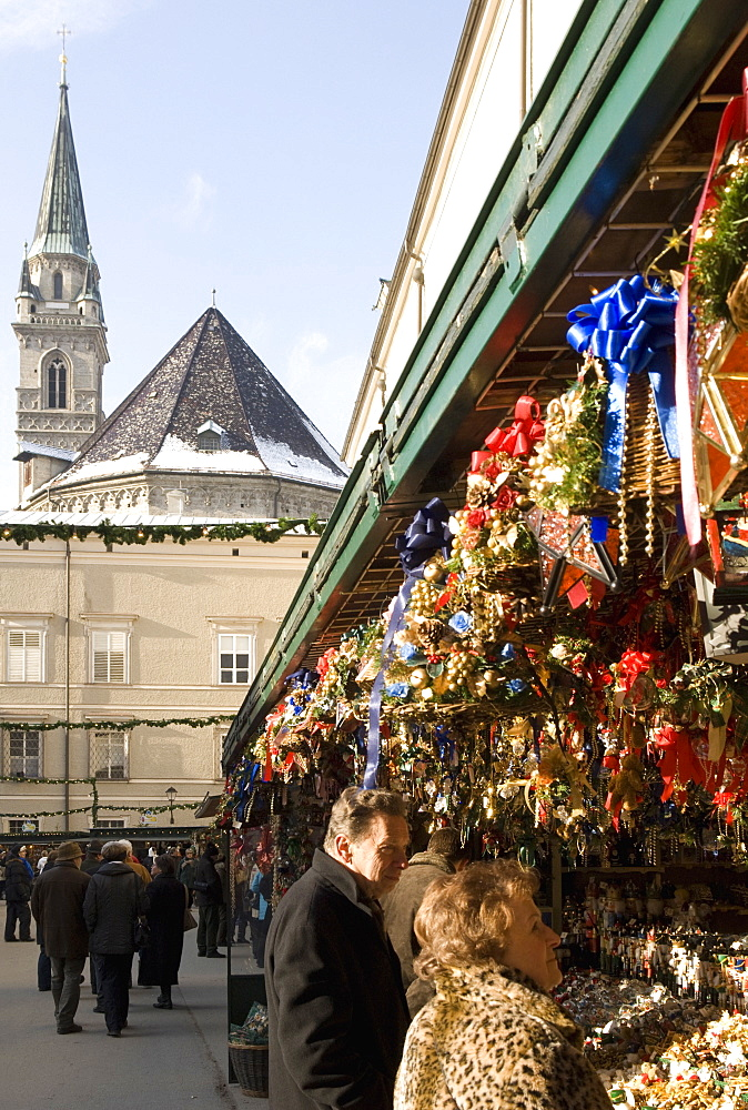 Stall selling Christmas decorations with towers of Franziskanerkirche churchbehind, Historical Salzburg Christkindlmarkt (Christmas market), Domplatz, Salzburg, Austria, Europe