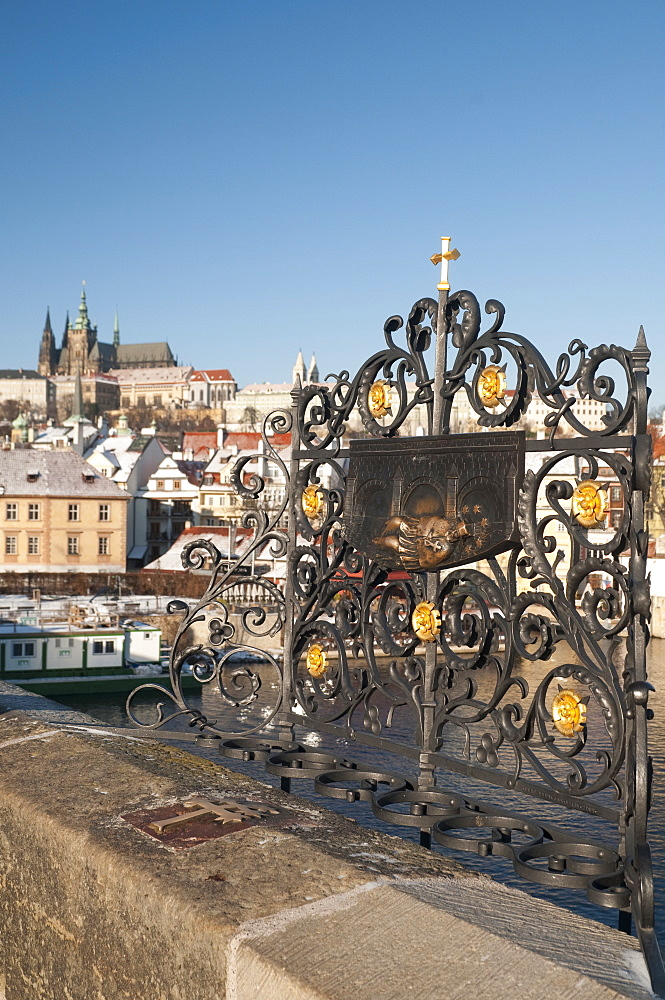 St. John of Nepomuk (Jan Nepomucky) shrine with cross at Charles Bridge with snow-covered Prague Castle and Mala Strana in background, UNESCO World Heritage Site, Prague, Czech Republic, Europe