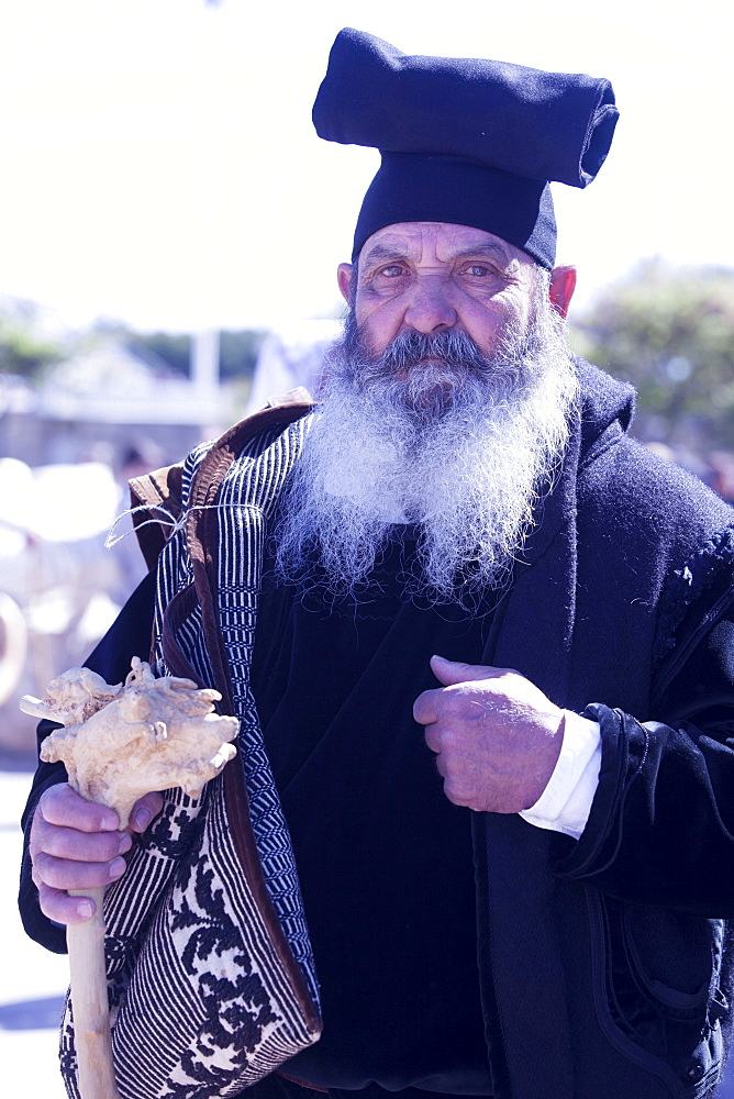 Man wearing the traditional Berritta Sardinian hat and carring the traditional double Sardinian sac, St. Antioco celebrations, Sant'Antioco,Sardinia, Italy, Europe